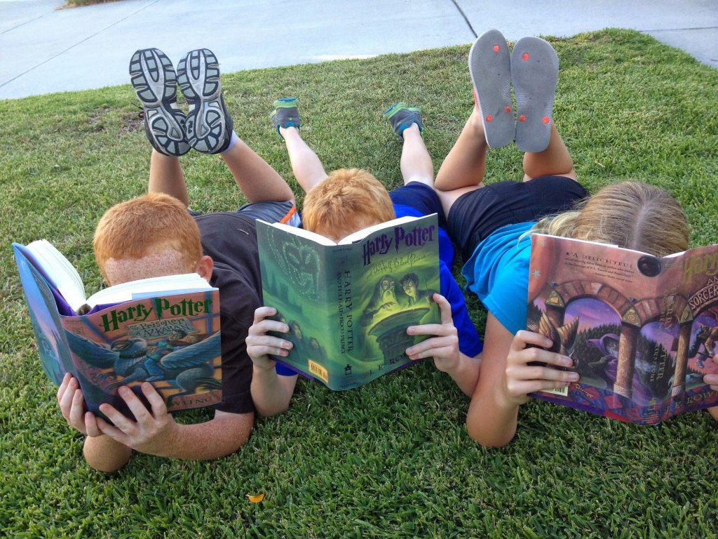 Fotografía de 3 niños leyendo cada uno un libro de Harry Potter.