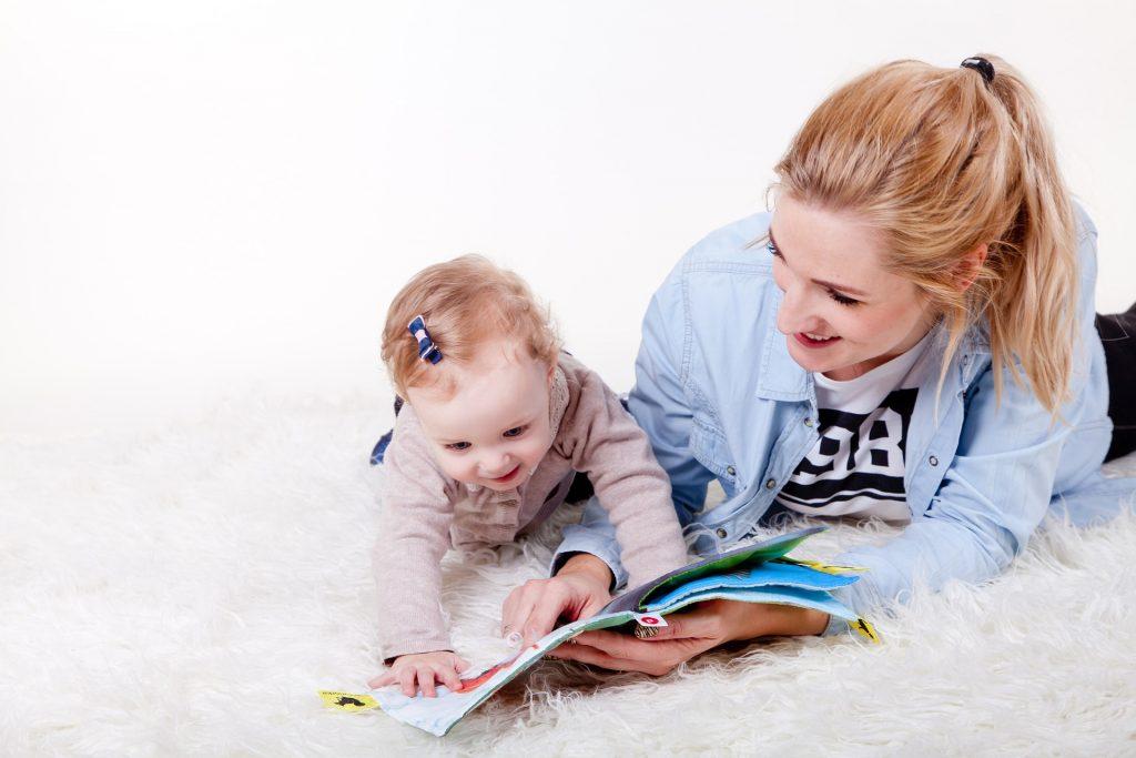 fotografia de una niña leyendo un libro junto a su madre
