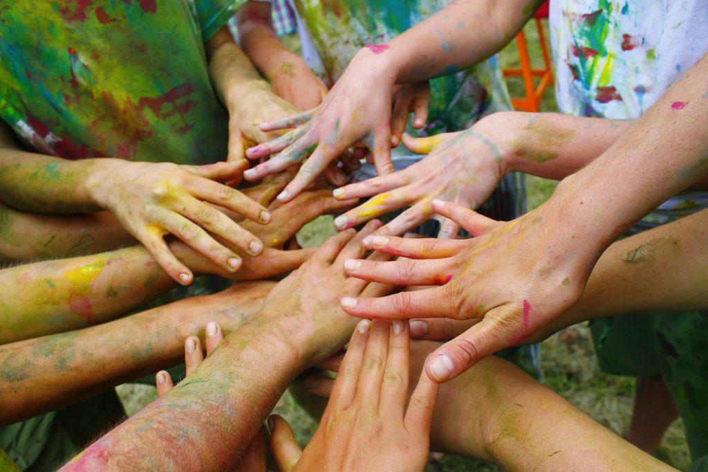 Foto de manos con pintura, uniéndose.