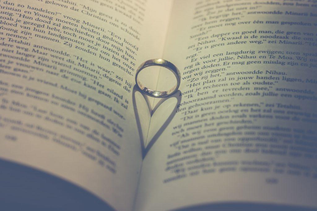 Imagen de un libro con un anillo en el medio, haciendo la sombra de un corazón.