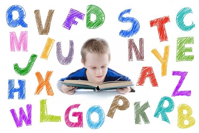 Imagen de un niño leyendo un libro. Y un montón de letras de colores a su alrededor, flotando.