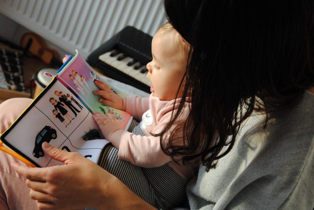 Imagen de una madre leyendo con su hija un libro de tela. - La hora de dormir en inglés