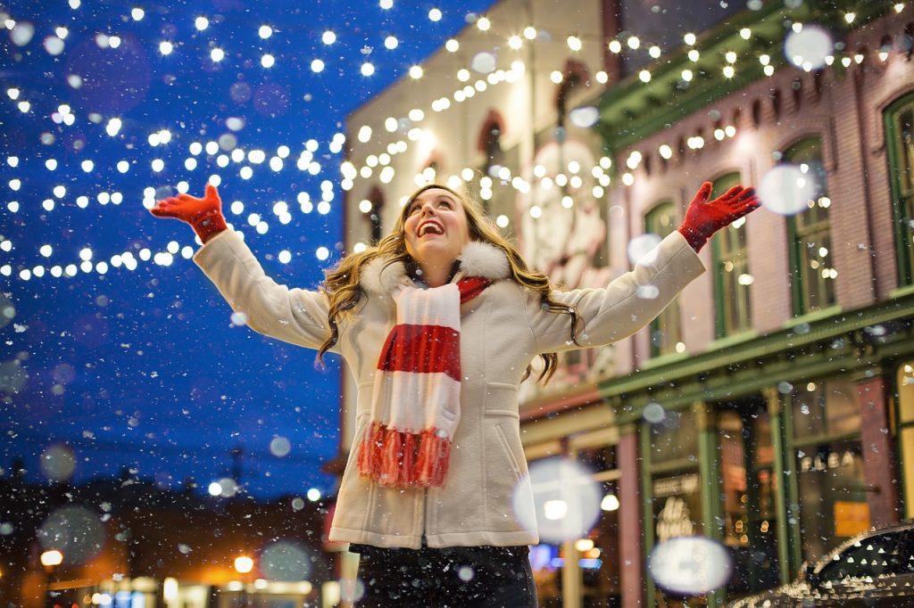 una mujer con los brazos abiertos disfrutando de la nieve caer