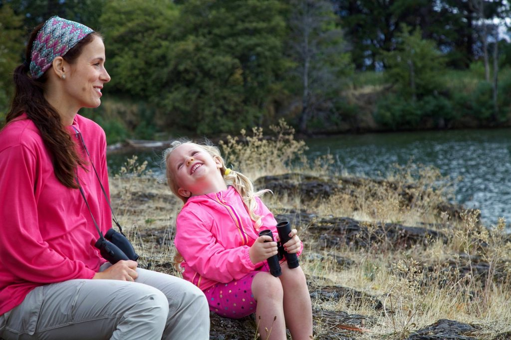 madre e hija mirando al rio con binoculares