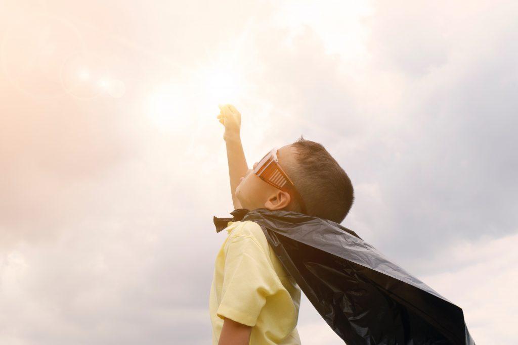 Niño con mano arriba haciendo el superheroe
