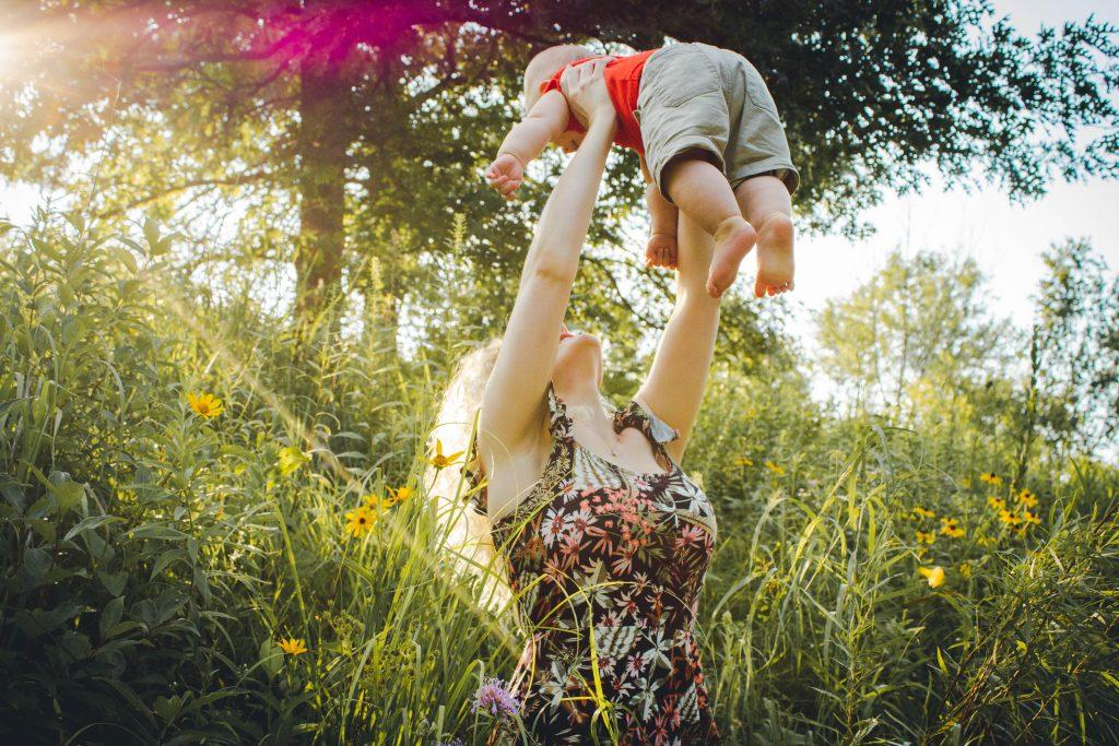 Imagen de una madre agarrando a su hijo en el aire- empezar a criar bilingüe