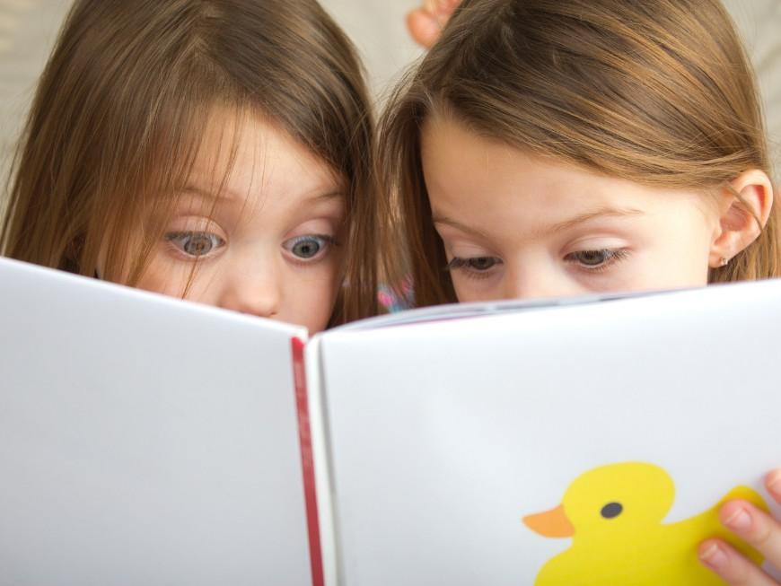Niñas sorprendidas al leer un libro