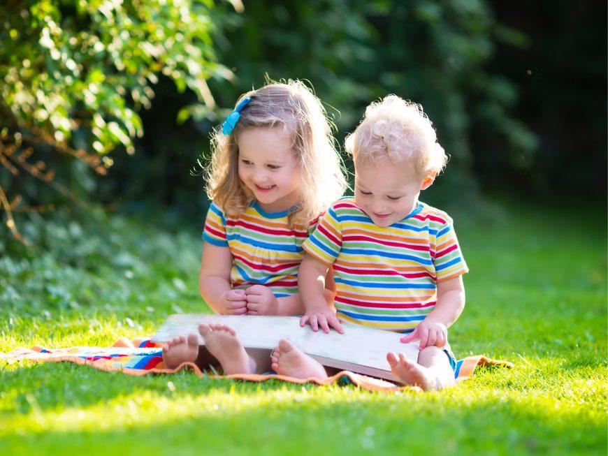 Dos niños leyendo en el jardín